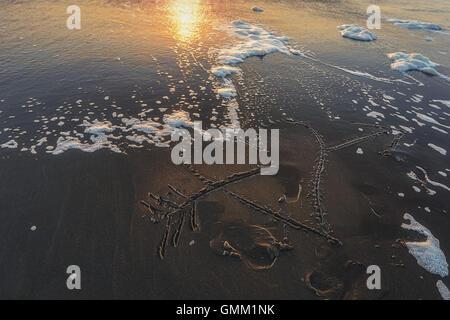 Cuore trafitto da una freccia disegnata sulla spiaggia sabbiosa lambita dalle onde. Foto Stock