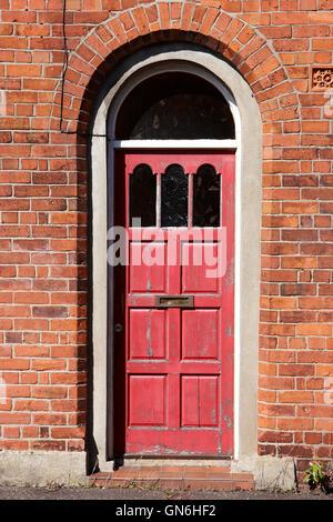 Peeling vernice rossa in una porta di legno in un portale ad arco di mattoni rossi in stile vittoriano fino a due Foto Stock