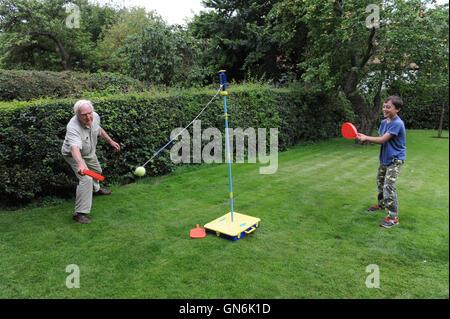 Nonno Swingball giocando con il suo nipote nel giardino. Foto Stock