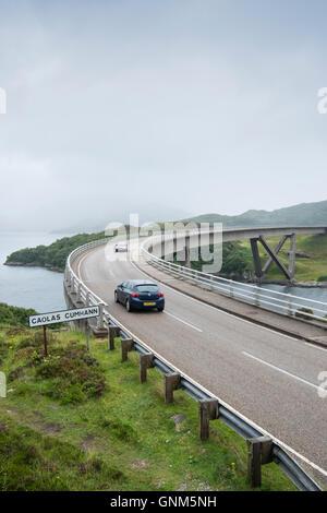 Il traffico sul ponte Kylesku attraverso il Loch un Chairn Bhain in Sutherland, Scozia, parte della costa Nord 500 scenic drive