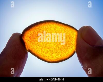 Wet orange pezzi di vetro levigato dal mare e cielo blu Foto Stock