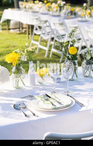 Eleganza tavolo bianco, verde e fiori di colore giallo del tema, il fuoco selettivo. (Set) Foto Stock