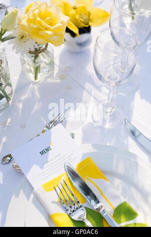 Close up eleganza tavolo bianco, verde e fiori di colore giallo del tema, il fuoco selettivo. (Set) Foto Stock
