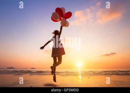 Fantasia, felice ragazza jumping con palloncini multicolori al tramonto sulla spiaggia, volare, seguire il tuo sogno Foto Stock