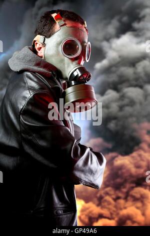 Uomo armato con maschera a gas su sfondo di esplosione Foto Stock
