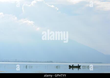 Barca da pesca nel lago con il cielo nuvoloso di riflessione, alla Contea di Dali, nella provincia dello Yunnan Foto Stock