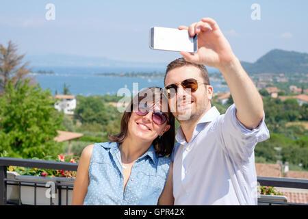 Giovane tenendo selfie durante le loro vacanze Foto Stock
