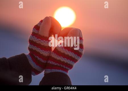 Donna in mani guanti invernali il simbolo del cuore di uno stile di vita a forma di sentimenti e di concetto con la luce del tramonto natura sullo sfondo Foto Stock