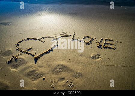 Cuore e freccia disegnata sulla sabbia in spiaggia. Il concetto di amore Foto Stock