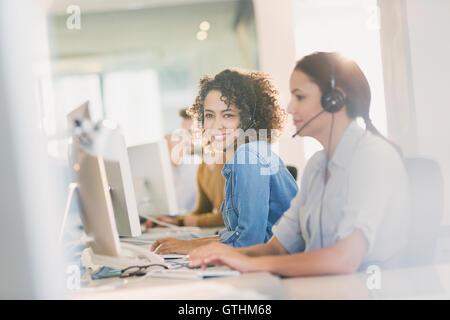 Ritratto sorridente imprenditrice con cuffia lavorando al computer in ufficio Foto Stock