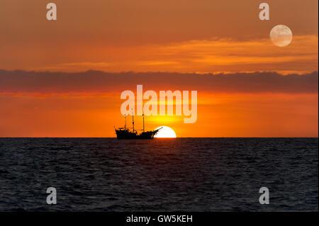 La nave dei pirati fantasy è un vecchio di legno la nave dei pirati con bandiere completo come il sole tramonta sull'oceano orizzonte in un colorato Cielo di tramonto.