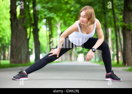Giovane bella donna stretching nel parco. Foto Stock