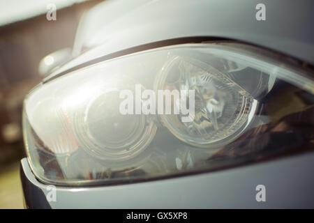 Primo piano della vettura anteriore fari allo xeno con luci riflessioni Foto Stock