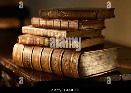 Libri Vintage stack su legno di antiquariato in superficie calda luce direzionale. Grunge e messa a fuoco selettiva.