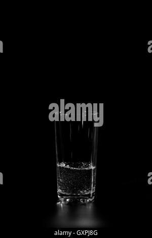 Bicchiere di vetro con acqua fresca su sfondo scuro Foto Stock