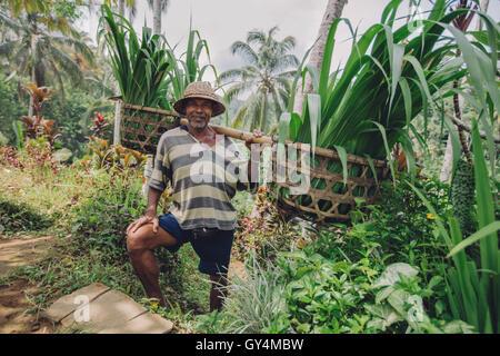 Colpo di vecchio uomo con le piantine sulle sue spalle. Senior sorridente agricoltore lavora nella sua azienda. Foto Stock