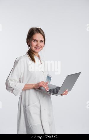 Donna sorridente medico che lavorano sul proprio portatile contro uno sfondo bianco Foto Stock