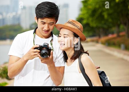 Giovani asiatici giovane turista in cerca in telecamera del monitor di controllo le foto scattate Foto Stock