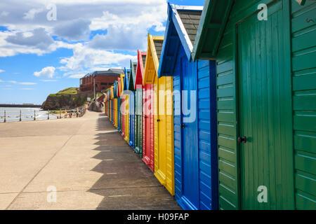 Riga della pittoresca spiaggia di capanne e le loro ombre, distante surfisti in mare, West Cliff Beach, Whitby, Foto Stock