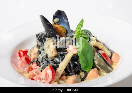 Spaghetti al nero di seppia, cozze, gamberi, calamari in una salsa cremosa con parmigiano Foto Stock