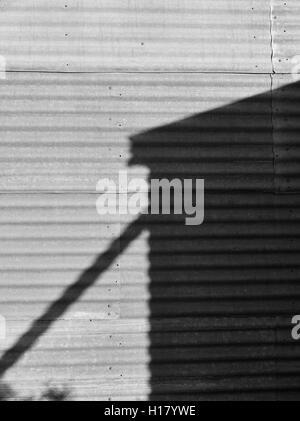 Immagine in bianco e nero outback australiano. Ombra di acqua del serbatoio sul ferro corrugato parete. Foto Stock