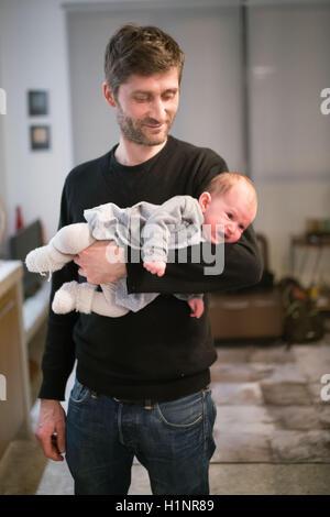 3 mese bambina nelle braccia di suo padre. Foto Stock
