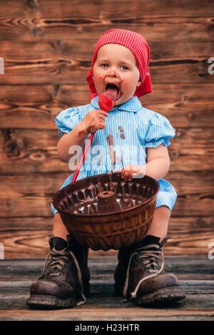 Tre-anno-vecchia ragazza di mangiare una torta al cioccolato miscela dalla teglia cosparsa sul viso, Austria Foto Stock