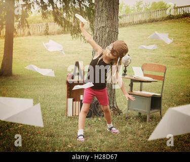 Un bambino piccolo che finge di essere un pilota di volare gli aeroplani di carta in una classe al di fuori di una Foto Stock