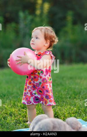 Bambina tenendo palla rosa sul prato in posizione di parcheggio Foto Stock
