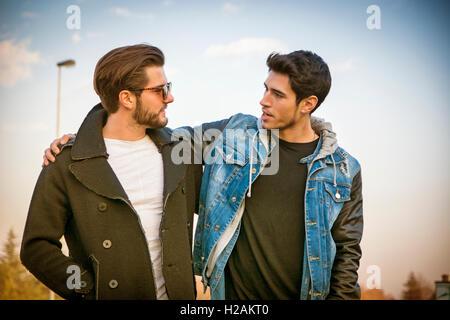 Due graziosi alla moda casual giovani uomini, 2 amici, in un parco urbano a piedi e chiacchierare insieme Foto Stock