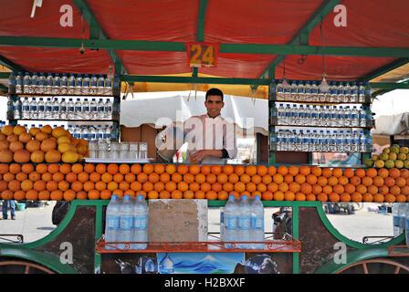 Un marocchino merchant versa il succo di arancia a vendere presso il suo stand presso la piazza Jemaa el Fna piazza Foto Stock
