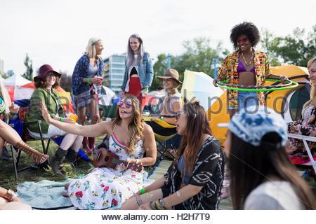 Amici appendere fuori a festival musicale estivo Campeggio Foto Stock