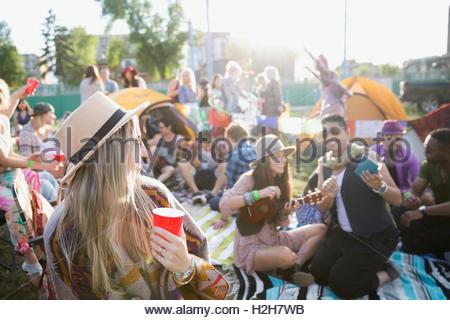 Giovani amici appendere fuori e beveva al festival musicale estivo Campeggio Foto Stock