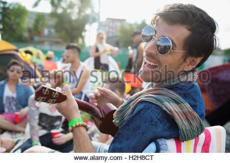 Ritratto di giovane entusiasta uomo giocando ukulele al festival musicale estivo Campeggio Foto Stock