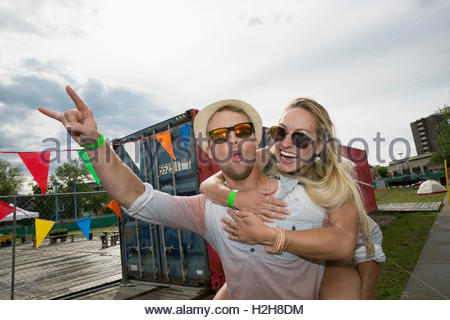 Ritratto entusiasta coppia giovane piggybacking e gesticolando al festival musicale estivo ingresso Foto Stock