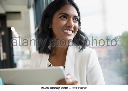 Ritratto sorridente imprenditrice con tavoletta digitale a guardare fuori dalla finestra di ufficio Foto Stock