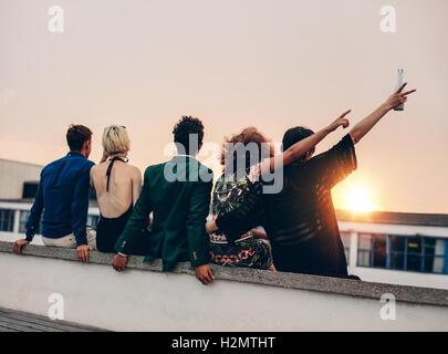 Gruppo di amici partying in terrazza con un drink. Giovani uomini e donne gustando un drink sulla terrazza sul tetto al tramonto.