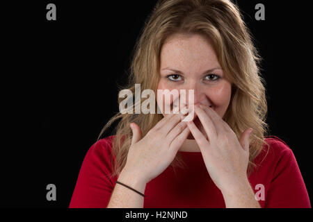 Timida donna bionda nascondendo il suo sorriso Foto Stock