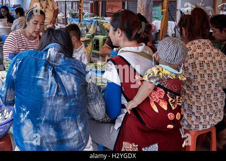Madre con bambino portato in un imbragatura posteriore e mangiare in un ristorante all'aperto. Thailandia S. E. Asia Foto Stock