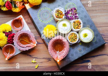 Diya lampade accese durante il Diwali celebrazione con fiori e dolci in background Foto Stock