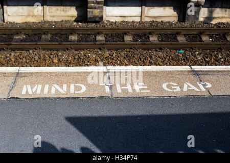 Mente il divario stencil sulla stazione ferroviaria platform Foto Stock