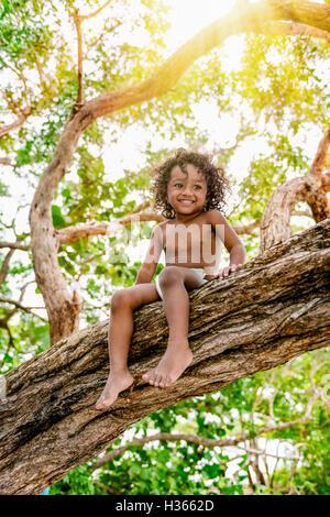 Tre anni bambino seduto su un albero il brunch nella giungla foresta avendo divertimento all'aperto Foto Stock