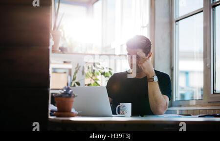 Colpo di giovane serio trovare idee mentre si lavora sul computer portatile. Imprenditore maschile seduto alla sua Foto Stock