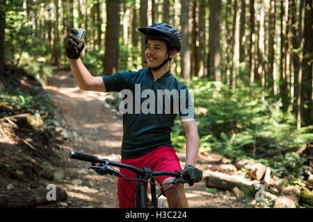 Ciclista maschio tenendo selfie sul telefono cellulare Foto Stock