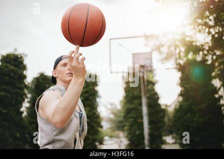 Giovane uomo di pallacanestro di bilanciamento sul suo dito sul tribunale aperto. Streetball player la filatura Foto Stock
