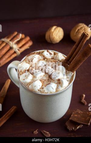 Cioccolata calda bevanda con marshmallows, scaglie di cioccolato e bastoncini di cannella sopra in legno rustico Foto Stock