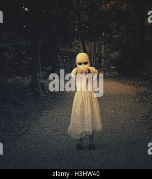 Un pauroso male ragazza fantasma che indossa un abito bianco e la faccia è a piedi in legno scuro con le sue mani verso l'alto. Utilizzarlo per un haunted paura Foto Stock
