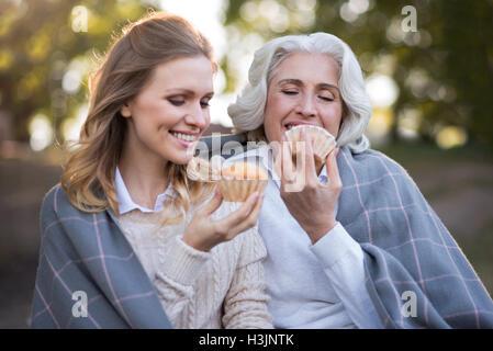 Due belle donne gioiosa seduto a terra Foto Stock