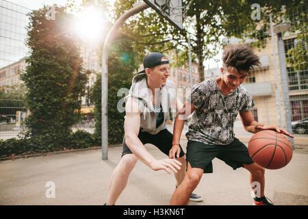 Due giovani amici giocare a basket sulla corte all'aperto e divertirsi. Streetball giocatori avente un gioco di Foto Stock