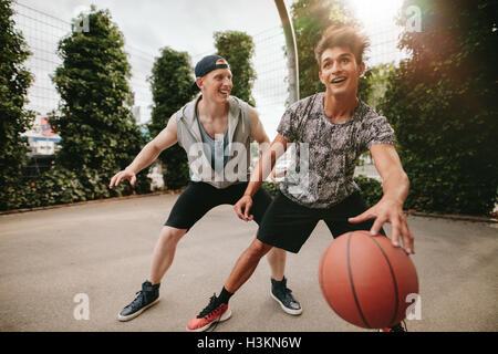 Due giovani amici giocare a basket e divertirsi. Streetball giocatori avente un gioco di basket sulla corte all'esterno. Foto Stock
